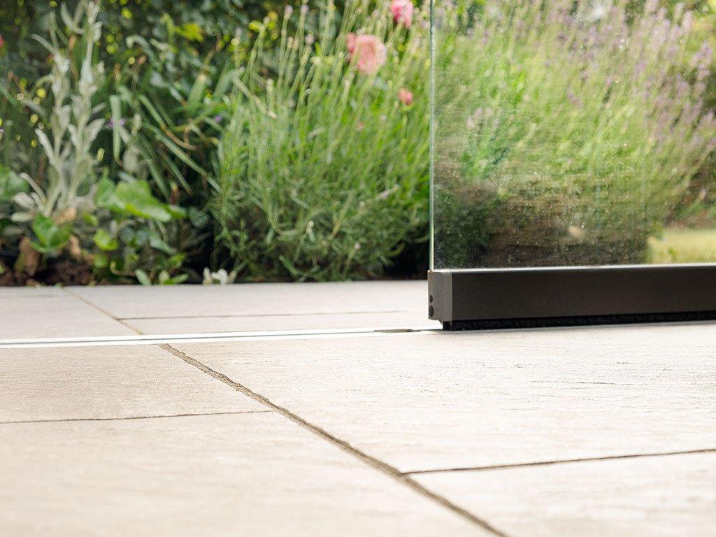 Moderne Terrasse mit Glas-Wintergarten und Bepflanzung in Bramsche